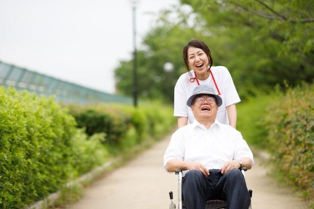 車椅子に乗る高齢の男性を女性の介護者が大笑いしながら進んでいる画像