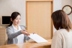 受付で話す女性と患者